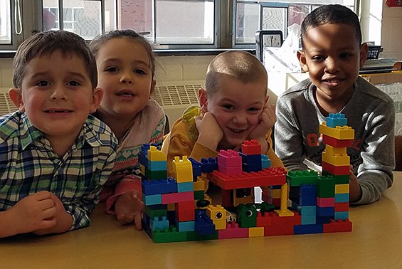 Tesago kindergarten students work as a team by learning to take turns and listening to one another to build a zoo in class.