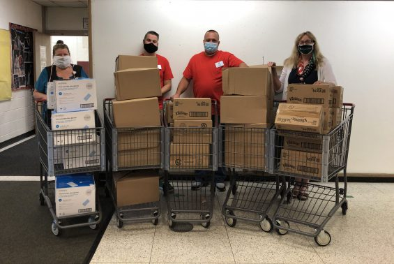 Four employees standing infront of shopping carts filled with boxes