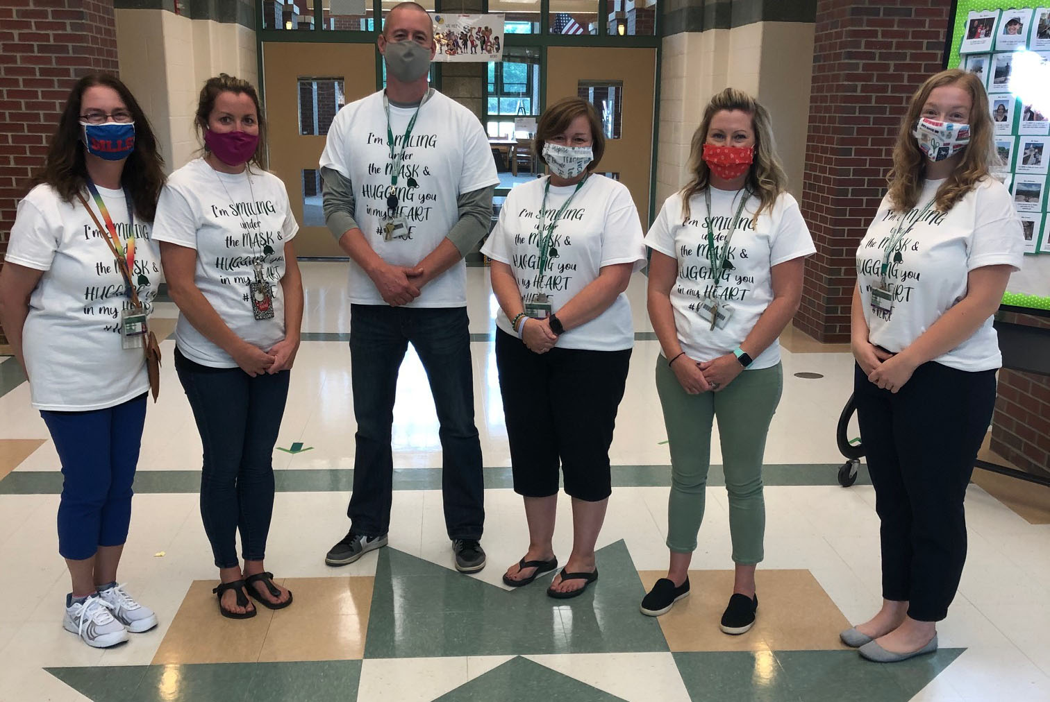 Shatekon teachers wearing tshirts that say they are smiling under the mask
