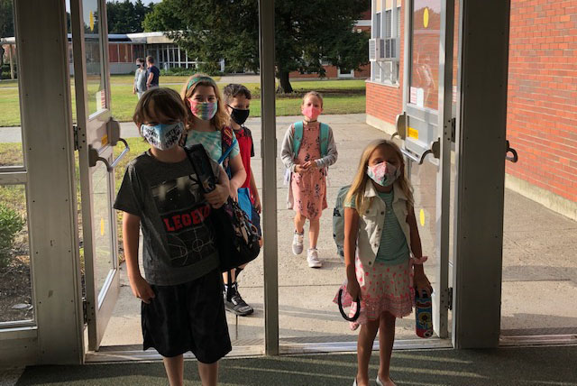 A group of students walking into Skano with masks on