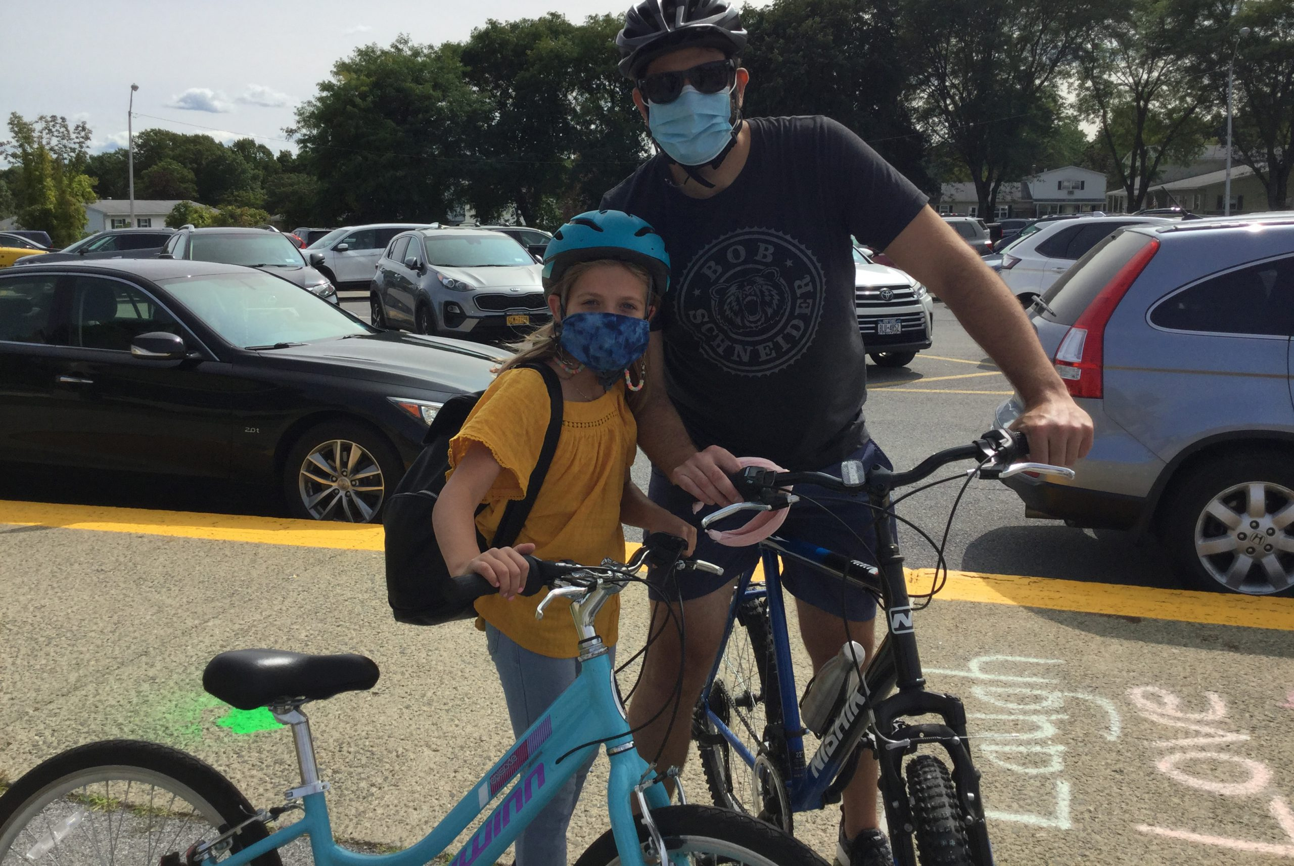 adult with student on bikes