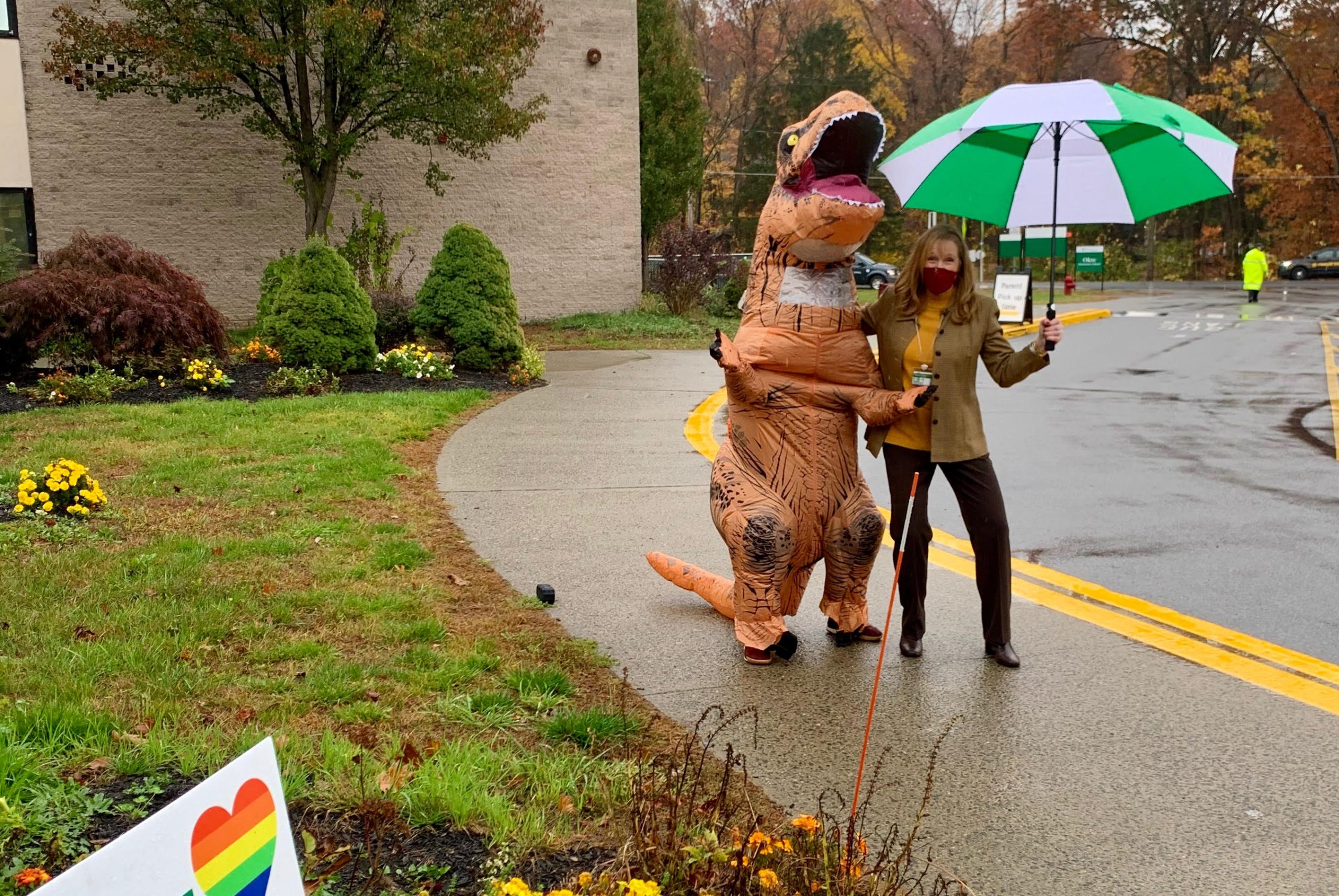 A Dancing Dinosaur greets Principal Strangis at Okte to brighten a rainy day! The kids loved dancing their way into school!