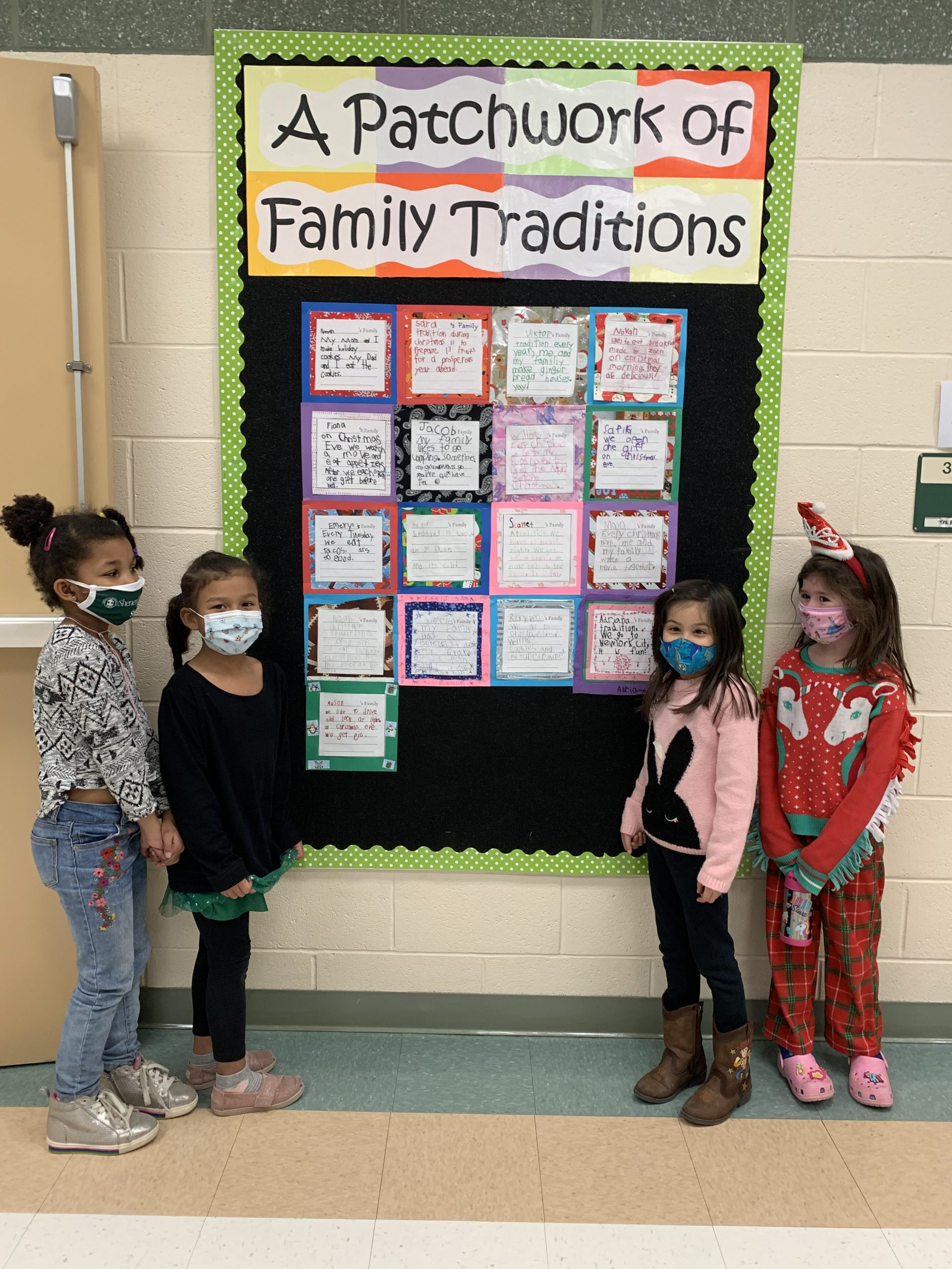 students in front of a bulletin board with sign that says A patchwork of Family Traditions
