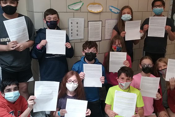 Students holding up article