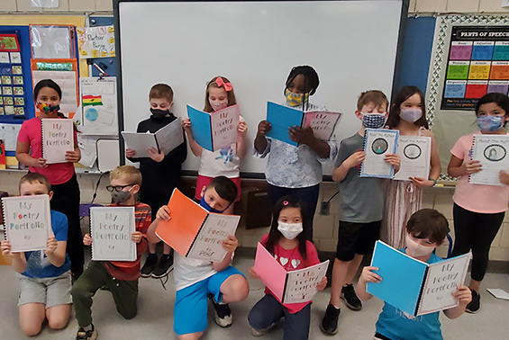 Arongen third graders in Mrs. Cahill's class show off their writing from Poetry Month in their published poetry books.