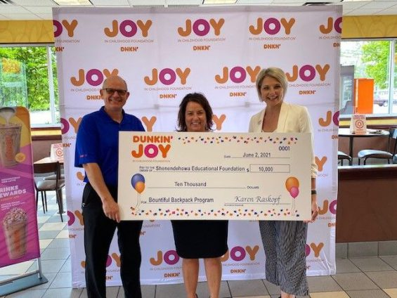 Three people pose with large check